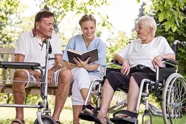 Pflegerin liest zwei Senioren ein Buch vor