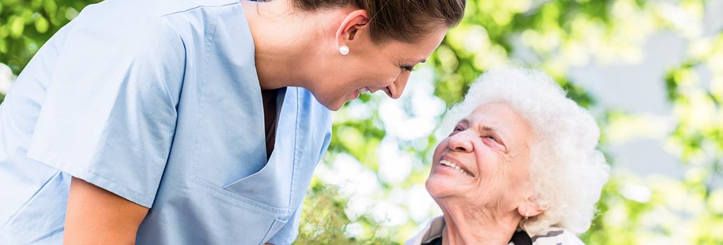 Pflegerin unterhält sich mit Frau